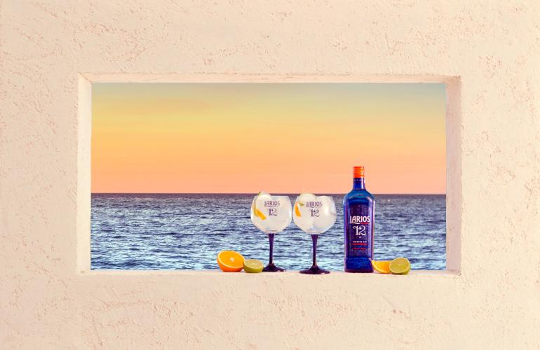 Copas y botella de Larios junto al mar