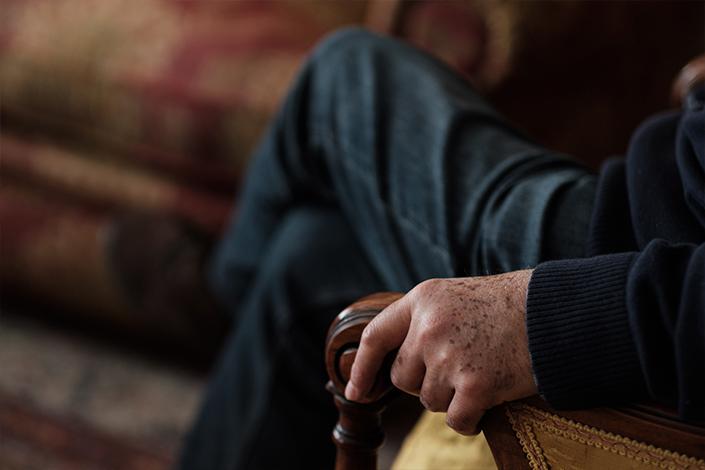 Juan, el marido de Charo, agarra la silla en la que está sentado mientras escucha el testimonio de su mujer