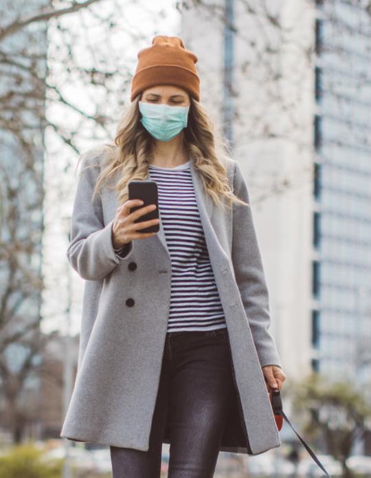 Una chica mira su móvil mientras pasea