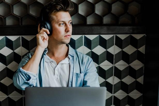 Millenial escucha a través de unos cascos en una cafetería
