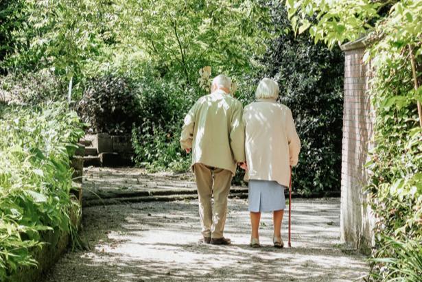 Pareja de jubilados paseando en un parque