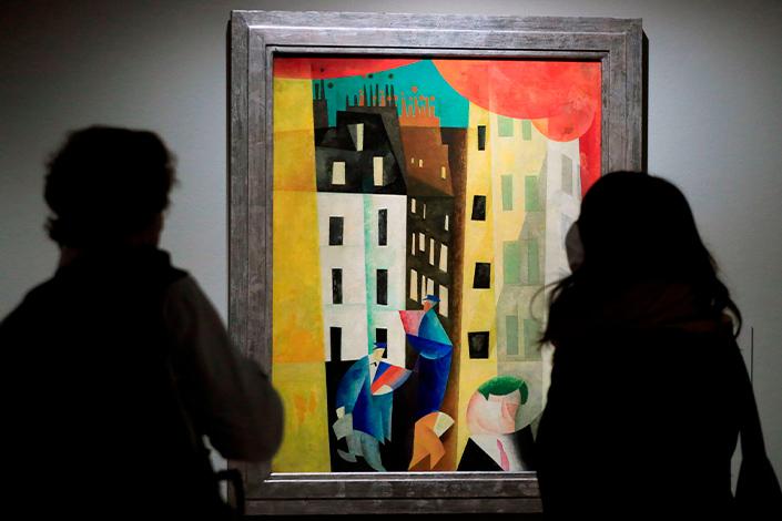 Dos personas personas contemplan un cuadro en el Museo  Nacional Thyssen-Bornemisza