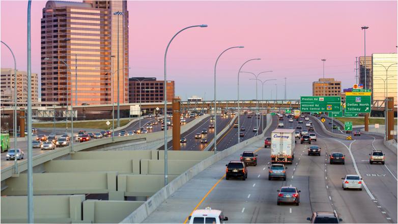 Autopista estadounidense junto a la ciudad de Dallas al atardecer