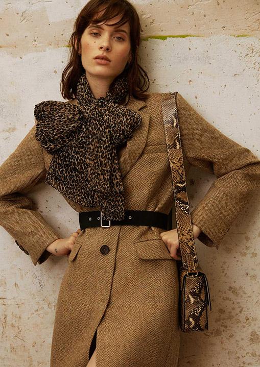Modelo con abrigo de Lloyd's, pañuelo de Fórmula Joven y bolso