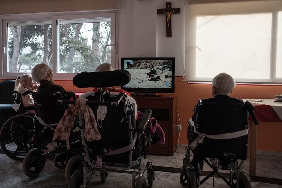 Un grupo de ancianos mira la televisión en uno de los comedores de la residencia