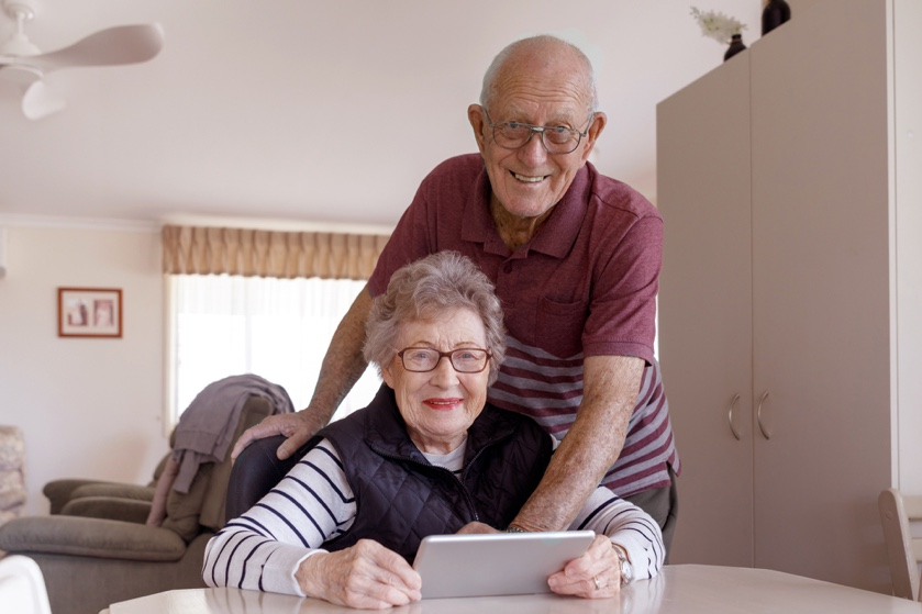 Pareja de ancianos son felices usando una tablet sin saber si la miran o no