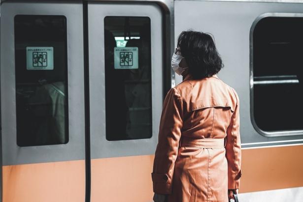 En la foto: una mujer con mascarilla a la espera del tren para ir a trabajar