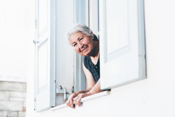 Mujer mayor asomada por una ventana