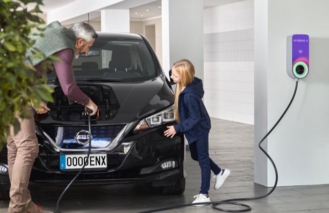 Un padre con su hija recarga su coche eléctrico