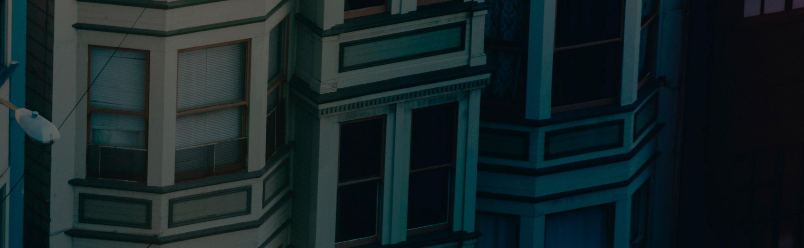 Una habitación con una planta junto a una persiana blanca echada