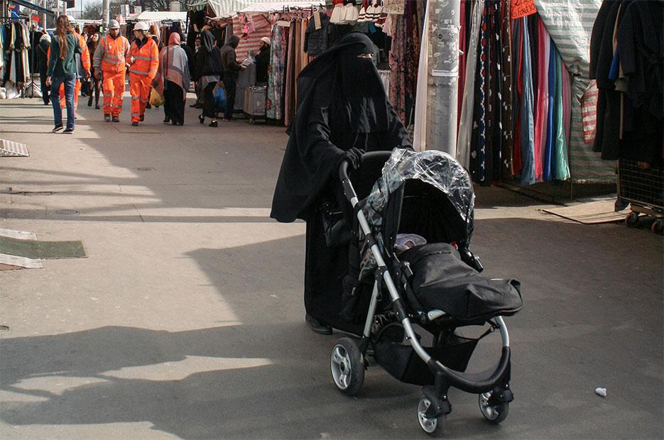 Una mujer vestida con 'niqab' pasea por un mercadillo londinense