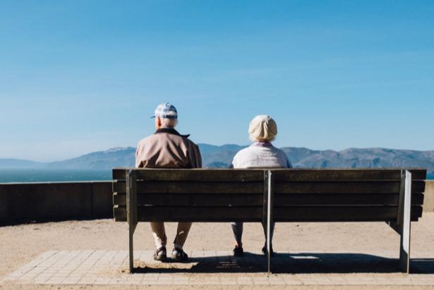 Pareja de jubilados sentados en un banco