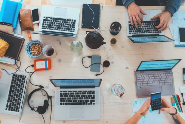 Un grupo de trabajadores con sus portátiles en una mesa