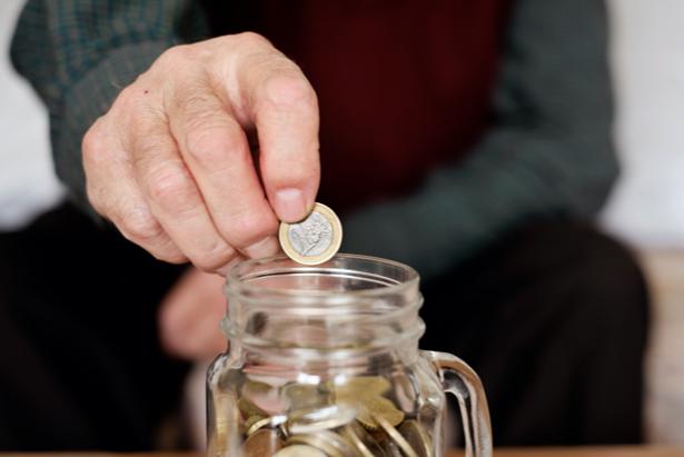Mano introduciendo dinero en una hucha